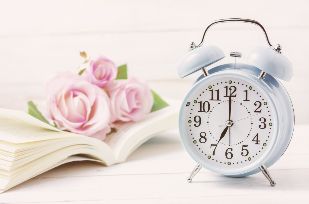 Blue retro alarm clock with book and pink pastel roses